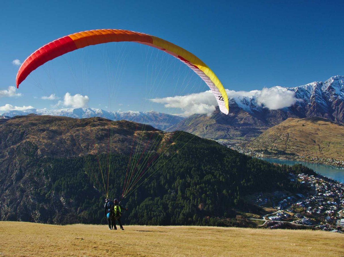 paraglide-over-the-mountains-and-water-surrounding-the-picturesque-city-of-queenstown-new-zealand
